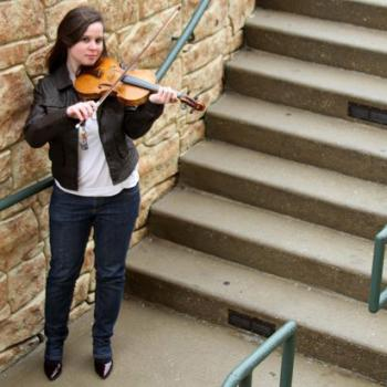 Allison plays her violin by a stone and concrete staircase