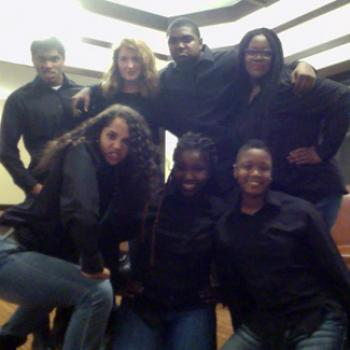 A group of 7 people dressed alike in black shirts and bluejeans