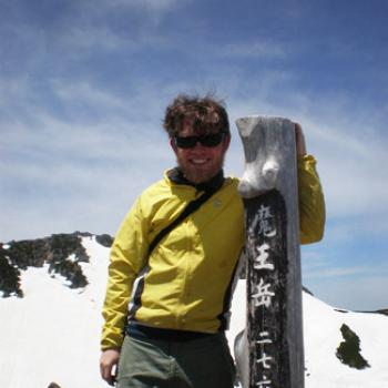 With a snowy mountaintop in the background, Andy stands at a wood post marked with Japanese writing