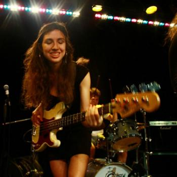 Arianna playing electric bass on stage
