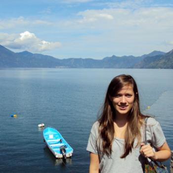 Ashley stands by a lake surrounded by mountains