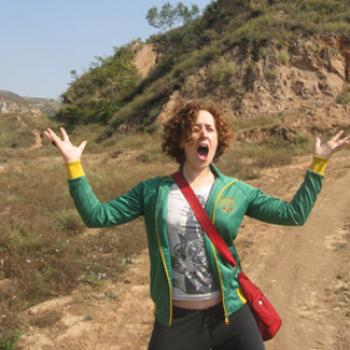 Standing by a hillside with hands raised and mouth wide open