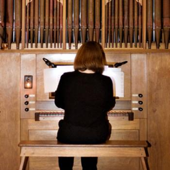 A woman plays a pipe organ