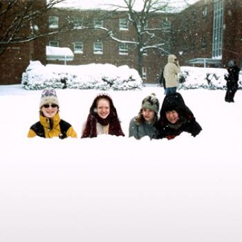 Four people peek over a snowbank
