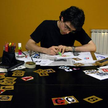 Christopher at a table with letter stencils, papers, and markers