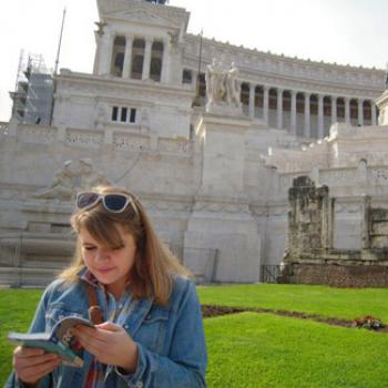 Claire reads a book in front of a classical structure with columns and statues
