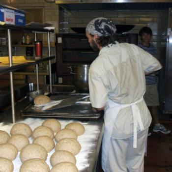 A man takes loaves out of a large oven