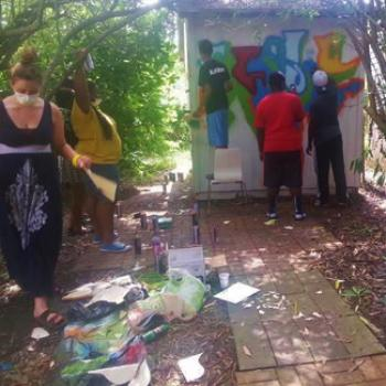 Volunteers paint a wall