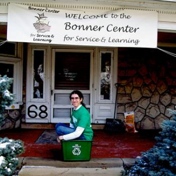 David sits in a recycling bin on the steps of the Bonner Center for Community-Engaged Learning, Teaching, and Research