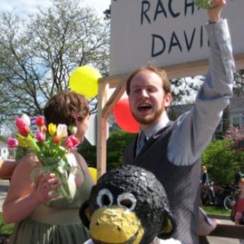 People outdoors with flowers and ballons. One is wearing a monkey head.