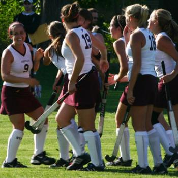 Field hockey players gather during a break in the action