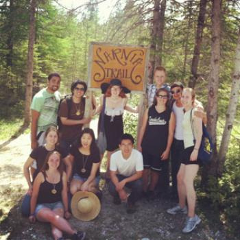 A group in the woods poses under a sign reading Narnia Trail