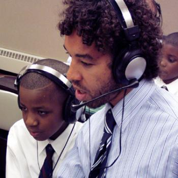 Wearing an audio headset, Jabali works with a couple of school-age boys