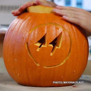 A pair of hands places the top on a jack-o-lantern