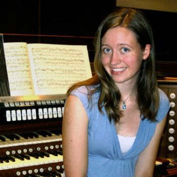 Young woman seated by an organ keyboard