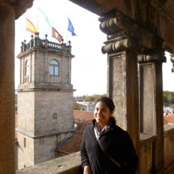 Jessica stands near a medieval turret which is flying flags of Spain and the EU