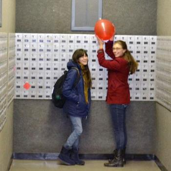 Jocie and a friend find a balloon by a wall of post office boxes