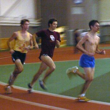 Three runners round the bend on an indoor track