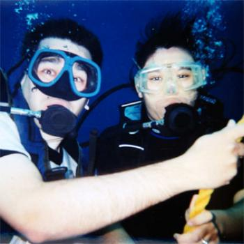 Two scuba divers underwater, bubbles rising from their masks