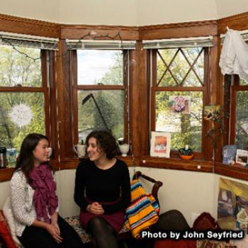 Two women seated in a room with several windows