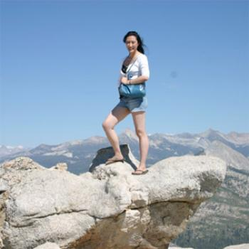 Juliette stands atop a high cliff, with mountains and sky behind her