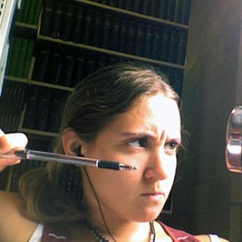 Kelsey aims a ballpoint pen at an off-screen target