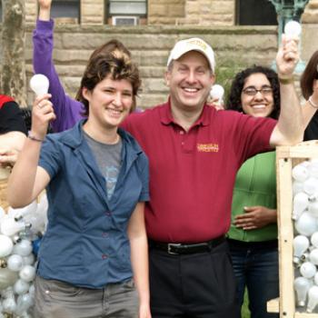 Students with President Krislov show off creates full of lightbullbs