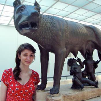 Lauren by a bronze sculpture of a wolf suckling two human infants