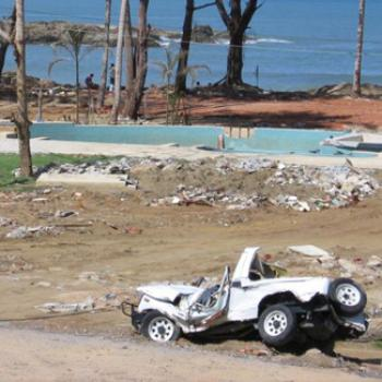 A mangled jeep and other debris by a beach.