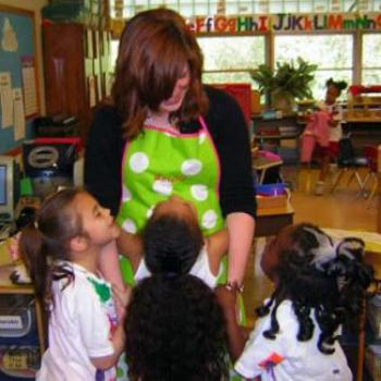 Mathilda receives hugs and smiles from young children in an elementary school classroom.