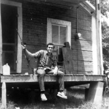 Sitting on the Freedom House porch, which rests on cinder blocks, Matthew holds a rifle. Black and white photo circa late 1960's.