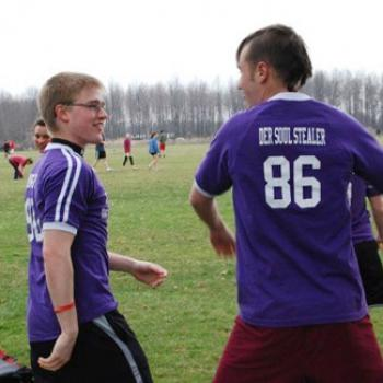 Soccer players on the sidelines. One wears a short with number 86 and the name Der Soul Stealer.