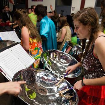 Maya reads sheet music while practicing on steel drums.