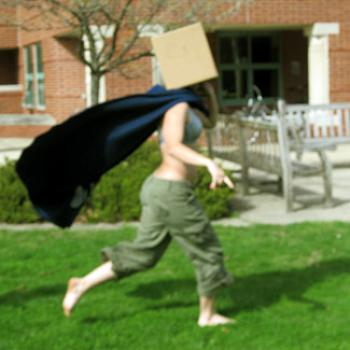 Her identity concealed by a cardboard box over her head, a woman runs in the grass, her cape flapping behind her.