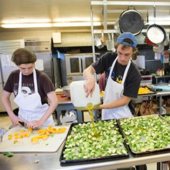 Two student cooks prepare vegetables in large quantities.