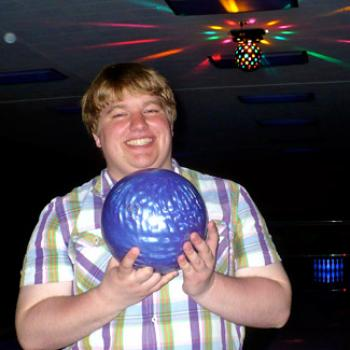 Patrick holds up a bowling ball under colorful lights.