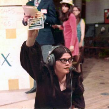 Woman wearing headphones and microphone on a production set.
