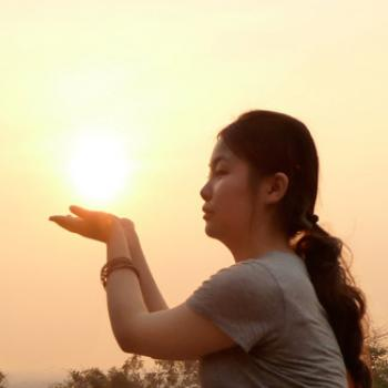 Qian extends her palms as if she's holding the sun.
