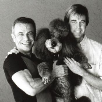 Robert and his spouse Steven pose with a fluffy poodle.