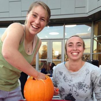 Rose and a friend have fun carving a pumpkin.