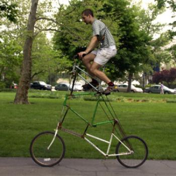 Sam rides atop an improbably tall bicycle.
