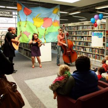 A trio plays music in the children's section of the public library.