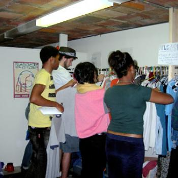 People looking through a rack of clothes.