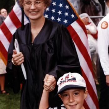 Sue holds her diploma in one hand and her son's hand in the other.