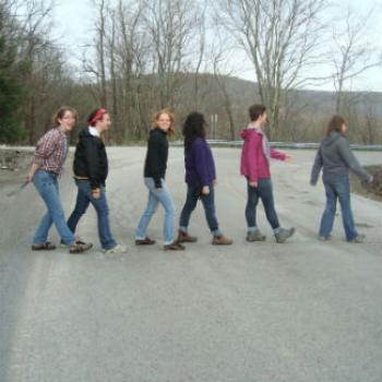 Six people walk across a road in single file.