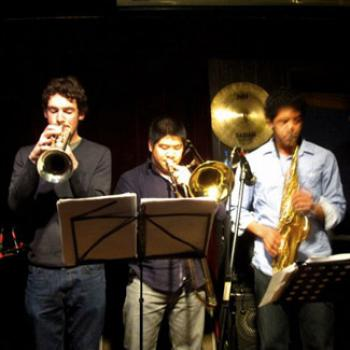 Three musicians play behind a music stand - trumpet, trombone, and alto sax