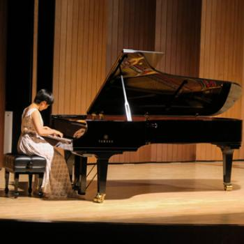Thanisa plays piano on stage.