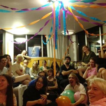 People at a party with streamers and balloons.
