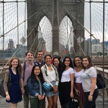 A group poses at a city bridge.