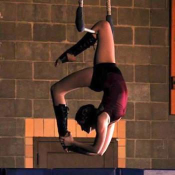 Zoe strikes an acrobatic pose on the trapeze.
